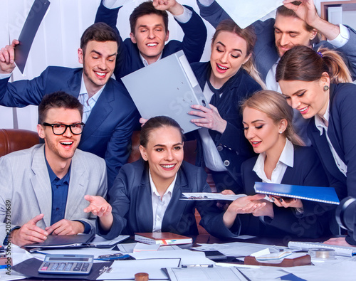 Foto Murales Business people office life of team people are happy with hand up sitting table and working papers. Cabinets with folders and jalousie background. Welcome reception at bank.