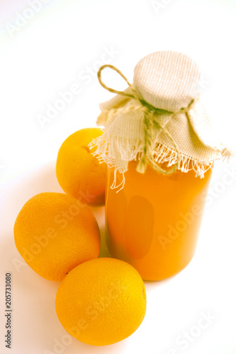 Glass transparent bottle with orange juice, close by there are three oranges. On a light background