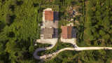 Perpendicular aerial view of an isolated country houses. Around the buildings there are the countryside and the hills. This house is located on the hills of Tuscany, in Italy.