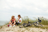 Women resting after riding bike on the beach - 205738671