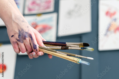 art painting hobby. creative leisure. talent inspiration creation and self expression concept. woman hand holding brushes.