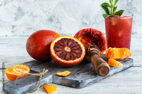 Blood oranges, citrus press and a glass of juice.