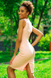 African model woman in pink dress, summer park outdoor