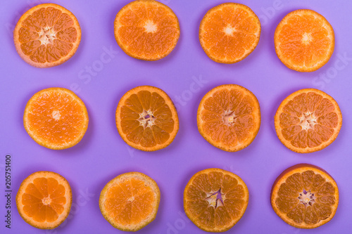 Fresh orange slices on violet background, top view