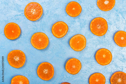 Fresh orange slices on blue background, top view