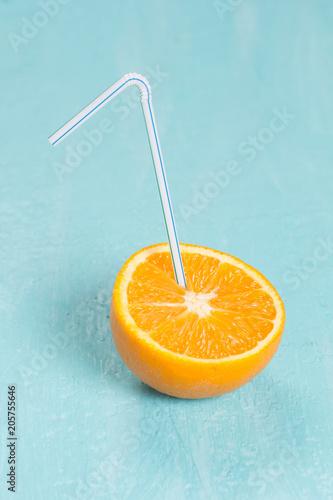 Half an fresh orange with a drinking straw