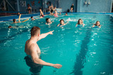 Instructor works with class in swimming pool