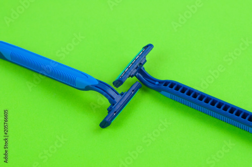 Two new blue plastic disposable razors with two blades and humid strip on blank green paper
