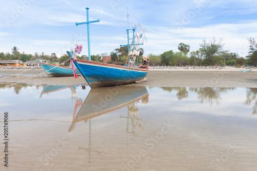 Fotobehang Schip Wooden fishing boat on the low tide beach