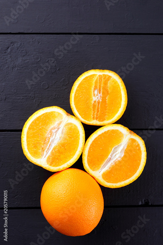 Fruits of oranges on a black wooden background, halves of oranges on wooden boards. Copy space. Citrus for Vegetarian Breakfast
