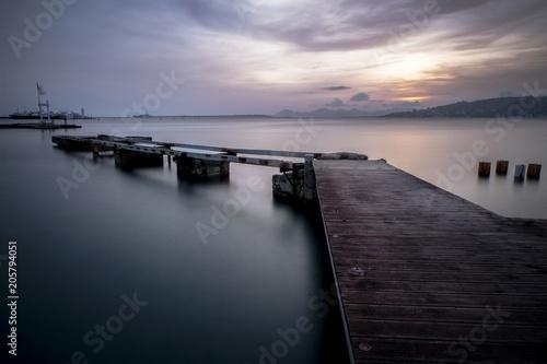 Foto Murales Un vieux ponton en ruine qui avance sur la mer lors d'un magnifique couché de soleil