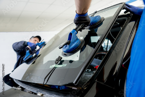 Automobile special workers replacing windscreen or windshield of a car in auto service station garage.