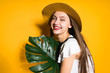 happy young girl model in a fashionable hat holds a green leaf and poses, laughs