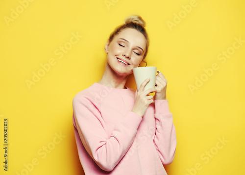 Młoda blond kobieta trzyma białą filiżankę z pojęciem, herbaty, kawy, stylu życia i jedzenia ,.