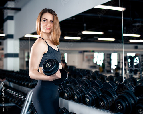 Plexiglas Fitness Girl doing bicep exercise with dumbbells in gym