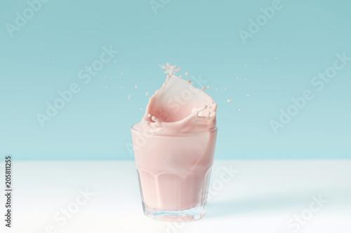 splashing drops of strawberry milkshake from glass on blue background