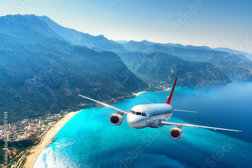 Fototapeta Airplane is flying over amazing mountains with forest and sea at sunrise in summer. Landscape with white passenger airplane, sky, islands and blue water. Passenger aircraft. Travel and resort. Tourism