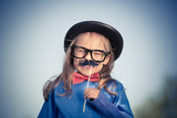 Outdoor portrait of funny happy little girl in bow tie and bowler hat. Retro stile. - 205824040