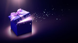 Blue open gift box with magical light