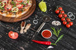 Vegetables, mushrooms and tomatoes pizza on a black wooden background. It can be used as a background - 205841626