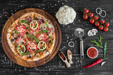 Vegetables, mushrooms and tomatoes pizza on a black wooden background. It can be used as a background - 205841631