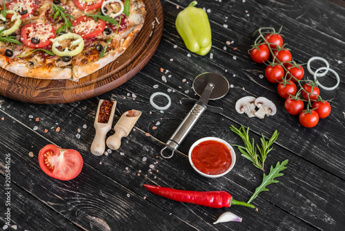 Wall mural Vegetables, mushrooms and tomatoes pizza on a black wooden background. It can be used as a background