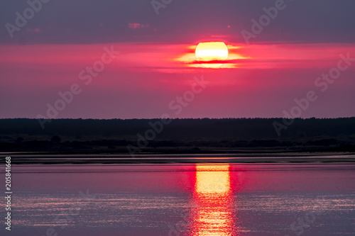Foto Spatwand Crimson Dramatic sunset over Anglesey in Wales seen from Caernarfon - United Kingdom