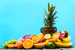 Tropical fruit mix on blue background, pile of colorful fruits on table and sunglasses, summer background
