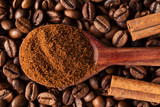 Ground coffee in a vintage spoon on coffee beans. - 205843689