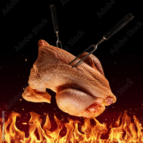Flying whole raw chicken above grill flames
