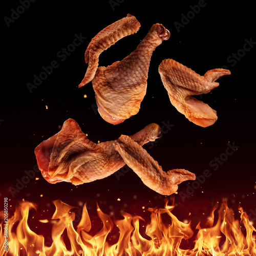 Flying raw chicken pieces above grill flames