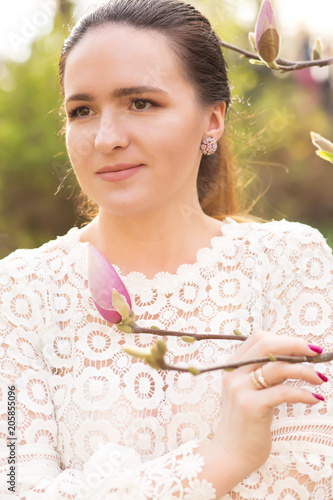 Fototapeta Closeup shot of attractive brunette model with nude makeup posing near the blooming magnolia flowers