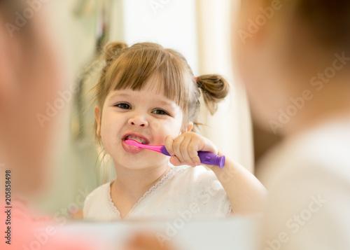 mother teaching her kid daughter teeth brushing