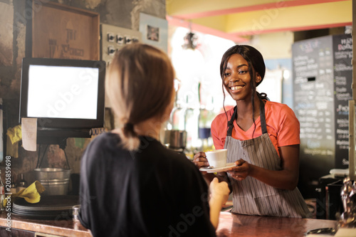 Foto Murales Smiling waitress serving a hot drink