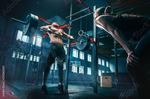 Fit młody człowiek podnoszenia sztangi w siłowni