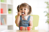Cute little child girl eating yogurt indoors