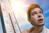 Hot weather concept. Young man is sweating. Thermometer is showing high temperature. Sun in background. - 205868248