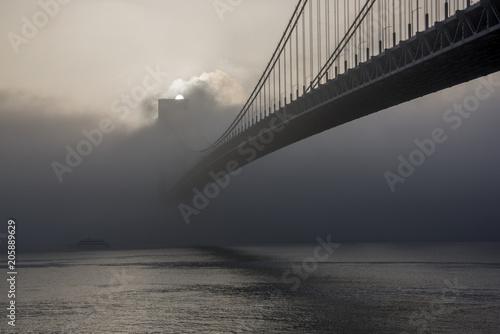 Bridge hidden in the fog at sunrise
