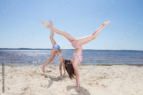 Fototapeta Two cute girls making cartwheel on a beach
