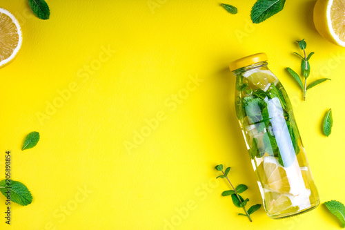 Leinwanddruck Bild Detox fruit infused water, citrus fruits and mint leaves on yellow background. Flat lay summer background with summer drink. Top view. Copy space