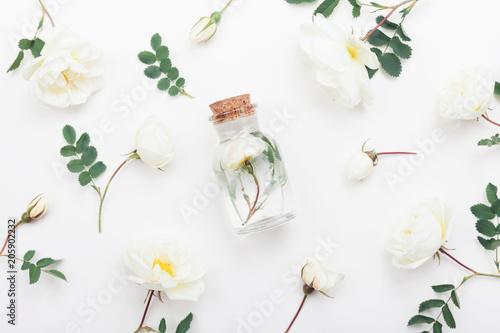 Szklany słoik z aromatyczną wodą i pięknymi kwiatami róży do spa i aromaterapii. Widok z góry i płaski styl.