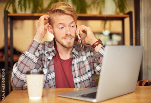 Portrait of trendy hipster using laptop while talking on mobile phone in cafe