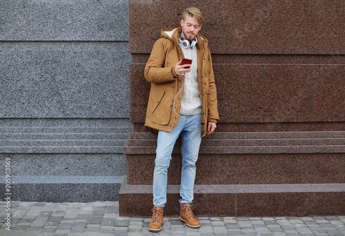 Handsome hipster using his smartphone outdoors