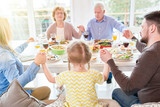 Portrait of big happy family saying grace at dinner holding hands during festive celebration in sunlight - 205903865