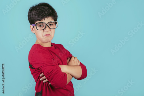niño enfadado con gafas sobre fondo azul