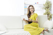 business woman with tablet sitting on the sofa in the nursery