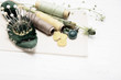 Sewing tools with dandelion flowers on vintage background