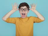niño gracioso con gafas que saca la lengua sobre fondo azul - 205919825