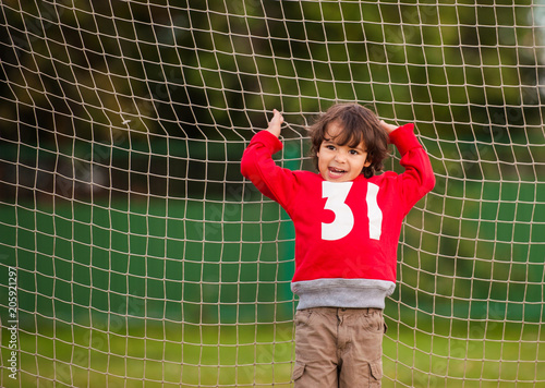 Fotobehang Voetbal the boy in the red hoodie at the football goal