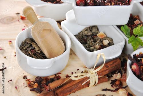 różne rodzaje herbaty suszonej w ceramicznych białych pojemnikach, zielonej herbaty, owocowej herbaty, różanej herbaty